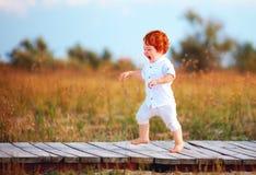 Bambino felice del bambino che esegue il percorso sul campo di estate Immagini Stock
