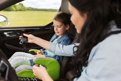 Bambino felice della legatura della donna con la cintura di sicurezza in automobile Fotografia Stock