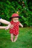 Bambino felice divertente sveglio in un vestito rosso che fa i suoi primi punti su un'erba verde in un soleggiato Immagini Stock