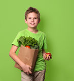 Bambino felice positivo in buona salute con il sacchetto della spesa di carta pieno di fre Immagine Stock Libera da Diritti