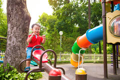 Bambino felice, ragazzo divertendosi sul campo da giuoco in parco Fotografia Stock Libera da Diritti