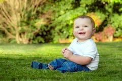 Bambino felice sorridente che gioca sull'erba Fotografia Stock