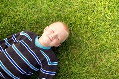 Bambino felice su erba verde fotografia stock