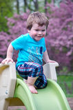 Bambino felice su uno scorrevole Fotografia Stock