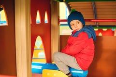 Bambino felice sul campo da giuoco variopinto del castello Ragazzino sveglio che gioca all'aperto nel tempo freddo di autunno Inf immagine stock