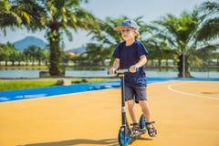 Bambino felice sul motorino di scossa dentro sul campo da pallacanestro I bambini imparano pattinare bordo del rullo Ragazzino ch fotografia stock