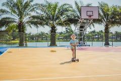 Bambino felice sul motorino di scossa dentro sul campo da pallacanestro I bambini imparano pattinare bordo del rullo Ragazzino ch fotografia stock libera da diritti