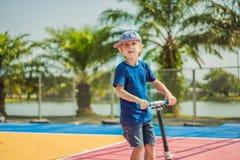 Bambino felice sul motorino di scossa dentro sul campo da pallacanestro I bambini imparano pattinare bordo del rullo Ragazzino ch immagini stock