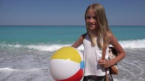 Bambino felice sulla spiaggia, bambina di risata sulle onde del mare della spiaggia sulla linea costiera 4K stock footage