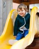 Bambino felice sullo scorrevole al campo da giuoco Fotografie Stock Libere da Diritti