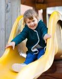 Bambino felice sullo scorrevole al campo da giuoco Fotografia Stock Libera da Diritti