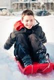 Bambino felice sullo scorrevole della neve Fotografia Stock Libera da Diritti