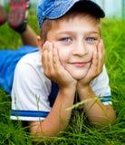 Bambino felice sveglio che pone sull'erba esterna Immagini Stock