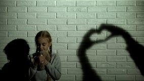 Bambino femminile che abbraccia orsacchiotto, l'ombra del cuore sul concetto della parete, di speranza e di gentilezza immagini stock libere da diritti