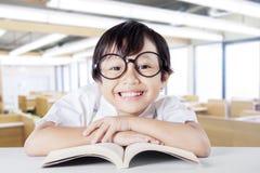 Bambino femminile che sorride alla macchina fotografica mentre libro di lettura Fotografia Stock