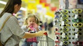 Bambino femminile felice con la sua abbastanza bella madre che sceglie gli occhiali da sole nel supermercato Ragazza sveglia con  archivi video