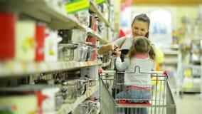 Bambino femminile felice e sua madre attraente dentro l'ipermercato che sceglie alcuni piatti o pentole che stanno insieme vicino archivi video