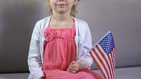 Bambino femminile sveglio con la bandiera americana a disposizione che si siede sofà, festa dell'indipendenza archivi video