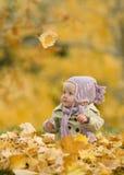 Bambino in fogli di autunno Fotografie Stock