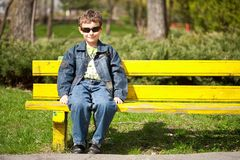 Bambino freddo che si siede sul banco immagini stock libere da diritti