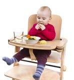 Bambino in giovane età che mangia nell'alta presidenza Fotografie Stock