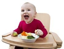 Bambino in giovane età che mangia nell'alta presidenza Fotografie Stock Libere da Diritti