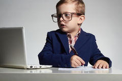 Bambino Giovane ragazzo di affari in ufficio bambino divertente in vetri che scrive penna immagine stock