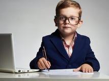 Bambino Giovane ragazzo di affari in ufficio bambino in vetri che scrive penna fotografia stock