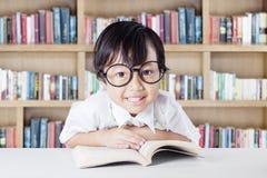 Bambino grazioso con i vetri ed il libro nella biblioteca Immagine Stock