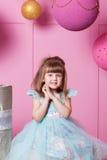 Bambino grazioso della ragazza 4 anni in un vestito blu Il bambino nella stanza del quarzo di Rosa ha decorato la festa Fotografia Stock