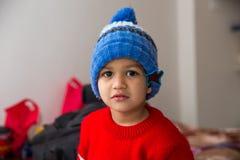 Bambino indiano sveglio che colpisce una posa nell'usura di inverno con un sorriso sveglio Fotografia Stock