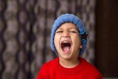 Bambino indiano sveglio che colpisce una posa nell'usura di inverno con una grande risata fotografia stock