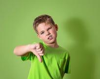 Bambino infelice, arrabbiato, dispiaciuto che dà gesto di mano dei pollici giù, isolato su fondo verde Fotografia Stock Libera da Diritti