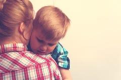 Bambino infelice triste che abbraccia sua madre Immagini Stock