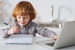 Bambino intelligente intelligente che fa il suo compito immagini stock