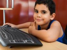 Bambino ispanico che lavora con un calcolatore Fotografia Stock