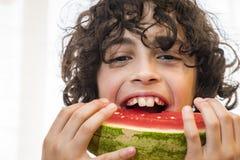 Bambino ispano che mangia la fetta fresca dell'anguria Fotografia Stock Libera da Diritti