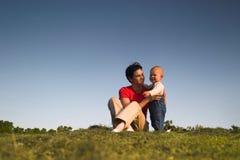 Bambino, madre, erba e cielo fotografie stock