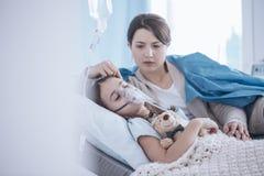 Bambino malato addormentato sostenente preoccupato della madre con la maschera di ossigeno e immagine stock