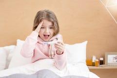 Bambino malato che tiene un termometro Fotografia Stock