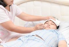 Bambino malato con febbre alta che si situa a letto Immagine Stock