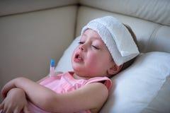 Bambino malato con febbre alta che si situa a letto Immagini Stock
