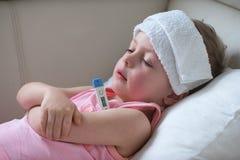 Bambino malato con febbre alta che si situa a letto Fotografie Stock Libere da Diritti