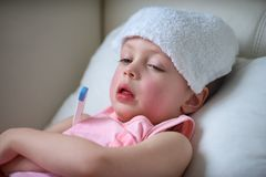 Bambino malato con febbre alta che si situa a letto Fotografie Stock