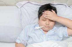 Bambino malato con febbre alta che si situa a letto fotografia stock
