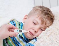 Bambino malato con febbre alta che si situano a letto e la madre che prende tempera Fotografia Stock
