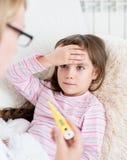 Bambino malato con febbre alta che si situano a letto e la madre che prende temperatura Fotografia Stock