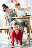 Bambino maleducato che si siede sotto la tavola durante la terapia per ADHD con la suoi madre e terapista professionista fotografia stock