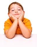Bambino maligno ed annoiato che si siede allo scrittorio Fotografia Stock Libera da Diritti