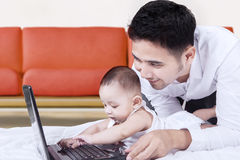 Bambino maschio che gioca computer portatile con il suo papà Fotografie Stock Libere da Diritti